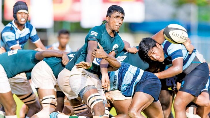 A tussle for the ball between Wesley and Isipathana players in the knockout schools rugby quarterfinal played at Sugathadasa Stadium on Monday.