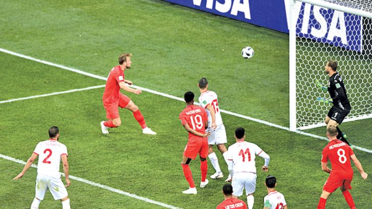 England's forward Harry Kane (2L) heads the ball and scores his second goal during the Russia 2018 World Cup Group G football match against Tunisia at the Volgograd Arena in Volgograd on Monday. - AFP