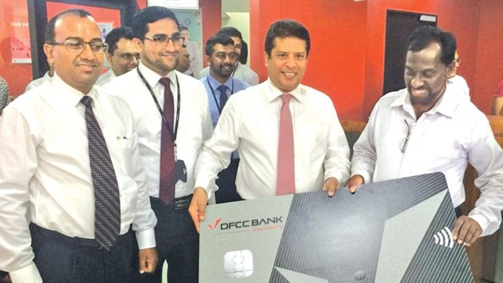 DFCC Bank CEO Lakshman Silva grants the first credit card to a customer