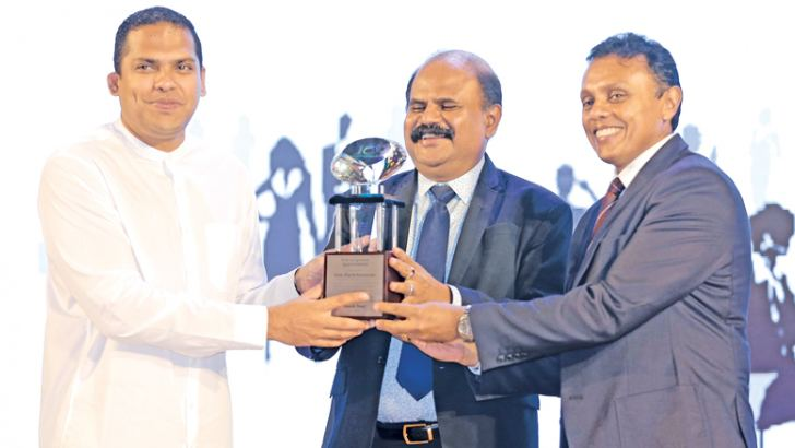 A token of appreciation presented to Harin Fernando, Minister of Telecommunication, Digital Infrastructure and Foreign Employment, Chief Guest at the SLT Human Capital Solutions by P.G. Kumarasinghe Sirisena, Chairman, Sri Lanka Telecom Group and Roshan Kaluarachchi, Chief Executive Officer HCS.