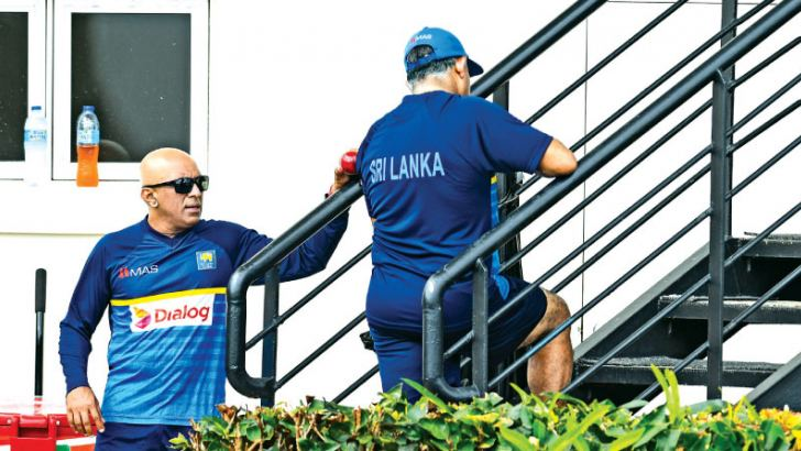 Holding up a session's play in a Test match which is contrary to the spirit of the game - Sri Lankan officials Chandika Hathurusingha (coach) and Asanka Gurusinha (manager) during the second Test against West Indies at Gros Islet. – AFP