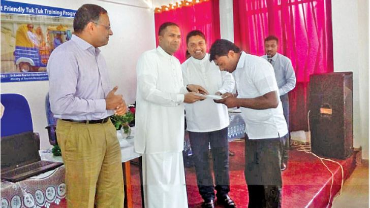 Minister Harin Fernando presenting a training certificate to a participant