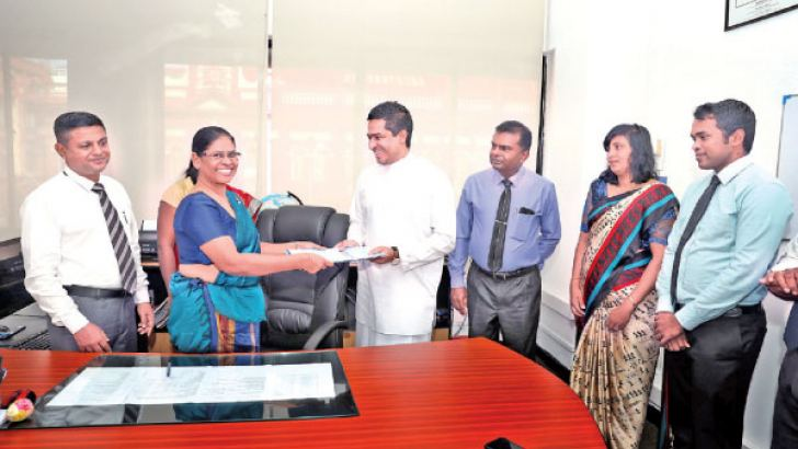 Damayanthi Karunarathna assuming duties as the new Controller General of the Imports and Exports Department in front of the State Minister, Sujeewa Senasinghe