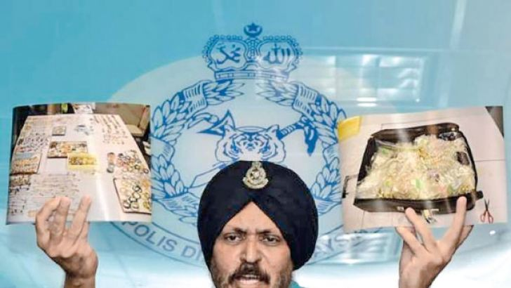 Malaysia's Commercial Crime Investigations Chief Amar Singh shows pictures of some of the valuable items seized from former Premier Najib Razak's luxury properties.