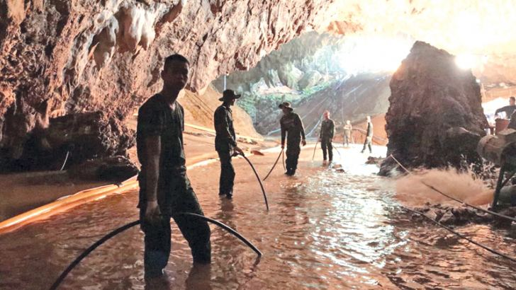 Thai rescue teams arrange a water pumping system at the entrance to a flooded cave complex.
