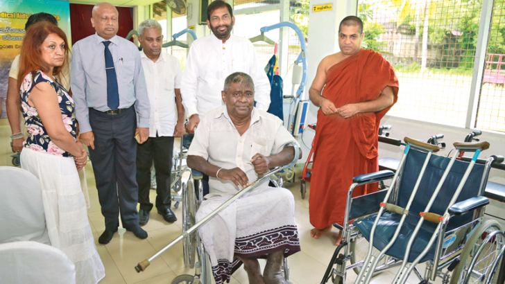 Minister Daya Gamage with the recipient of a wheelchair, at the event.  Picture by Shan Rambukwella