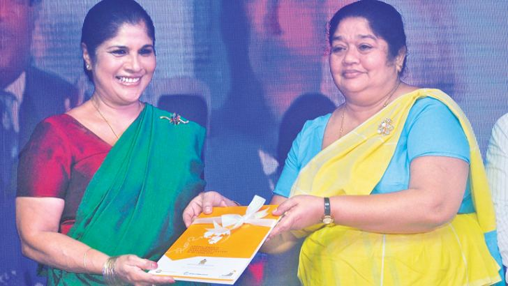 Women and Child Affairs Secretary Ashoka Alawatte presents a copy of the census to Women and Child Affairs Minister Chandrani Bandara, at Water's Edge, yesterday. Picture by Siripala Halwala