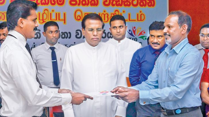 The first instalments of funds being handed over to a Grama Shakthi Janatha Samithi while President Maithripala Sirisena looks on. Picture by President's Media.