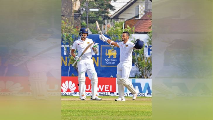 Sri Lanka opener Dimuth Karunaratne celebrates his century with acting captain Suranga Lakmal as the non striker on the first day of the first Test against South Africa at the Galle International Stadium yesterday. Pictures by Saman Mendis