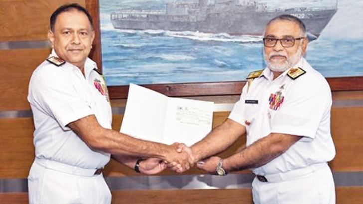 Chief Hydrographer of the Navy, Rear Admiral Sisira Jayakody hands over the cheque to Navy Commander Vice Admiral Sirimevan Ranasinghe