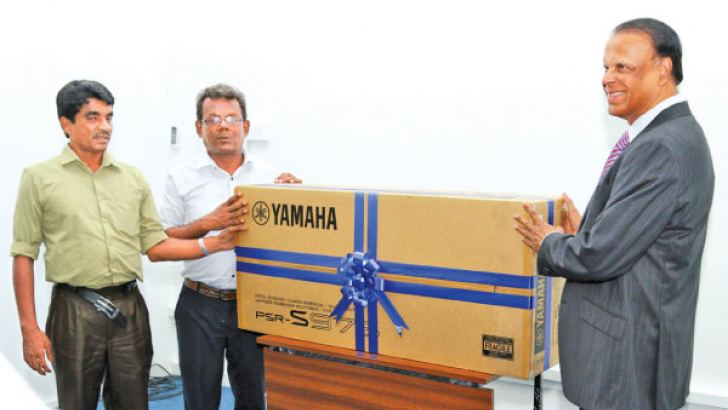 Group Chairman of Richard Pieris, Dr. Sena Yaddehige presenting a keyboard for a visually handicapped musician. Picture by Saliya Rupasinghe