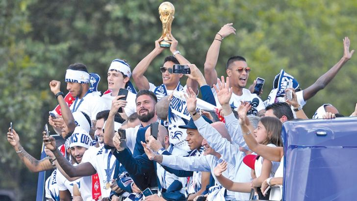 France's defender Raphael Varane (C) holds the trophy as he celebrates with teammates on the roof of a bus while parading down the Champs-Elysee avenue in Paris, on July 16, 2018 after winning the Russia 2018 World Cup final football match. AFP