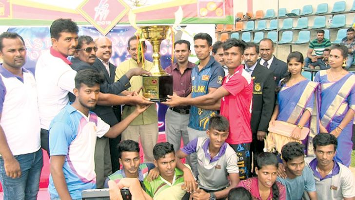 Batticaloa Government Agent M.Uthayakumar handing over the champion trophy to Trincomalee district team.