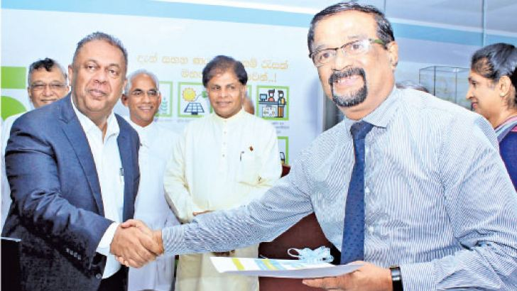 Minister of Finance and Mass Media,  Mangala Samaraweera handing over loans to an entrepreneur at the event. Picture by Saliya Rupasinghe