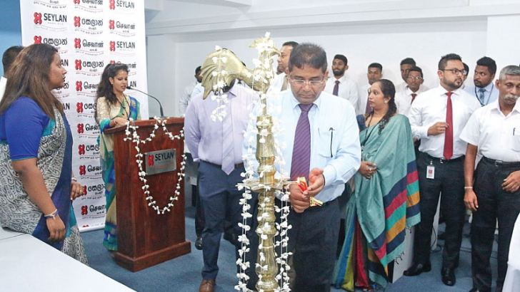 Kapila Ariyaratne Director and CEO of Seylan Bank lights the traditional oil lamp at the newly established SeylanSales Centre.