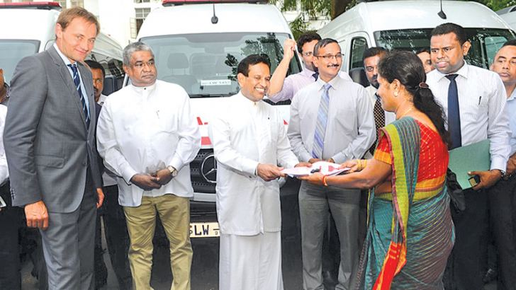 Health Minister Dr. Rajitha Senaratne hands over an ambulance to a hospital director while Health Deputy Minister Fizal Kassim and the representative from Austria looks on.