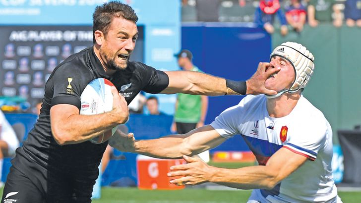 Kurt Baker (L) of New Zealand deflects a tackle from Manoel Dall Igna of France before scoring a try during their Championships quarterfinals game at the Rugby Sevens World Cup in the AT&T Park at San Francisco, California on Saturday. – AFP