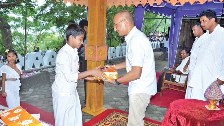 Nirmal Madanayake handing over school items.
