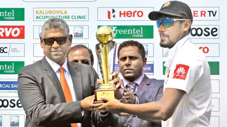 Sri Lanka's acting captain Suranga Lakmal receives the series trophy from Sports Minister Faiszer Mustapha. Pix by Susantha Wijegunasekera
