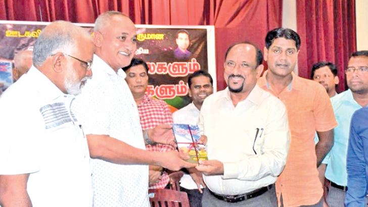 Parliamentarian A. L. M. Nazeer receives a copy of the book from chief guest Fisheries and Aquatic Resources Development and Rural Economy Affairs Deputy Minister M. S. S. Ameer.  Picture by I. L. M. Rizan, Addalaichenai Central Corr.