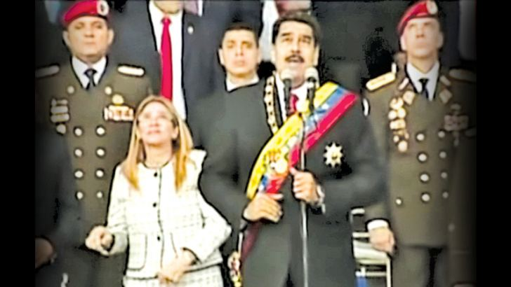 In this still from a video provided by Venezolana de Television, Venezuelan President Nicolas Maduro, delivers his speech as his wife Cilia Flores winces and looks up after being startled by and explosion in Caracas Venezuela on Saturday.