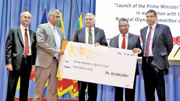 Prime Minister Ranil Wickremesinghe presenting the Rs. 50 million cheque to President of the National Olympic Committee of Sri Lanka Suresh Subramaniam at Temple Trees yesterday. Also in the picture (from left) Secretary General of NOC Maxwell de Silva, Sports and Provincial Councils Minister Faiszer Mustapha and Hatton National Bank Chairman Dinesh Weerakkody.   Pictures by Hirantha Gunathilaka