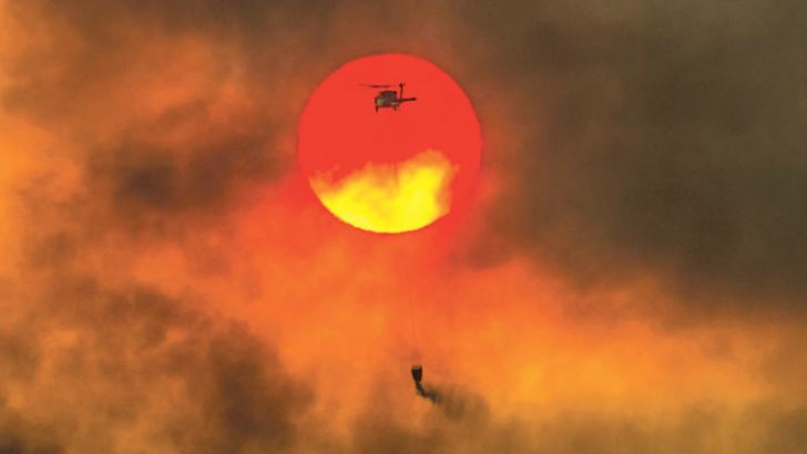 A firefighting helicopter makes a water drop as the sun sets over a ridge burning near Redding, California.