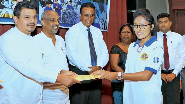 Mahaweli Development State Minister Weerakumara Dissanayake handing over a scholarship to one of the Mahaweli youth. Picture by Saman Sri Wedage
