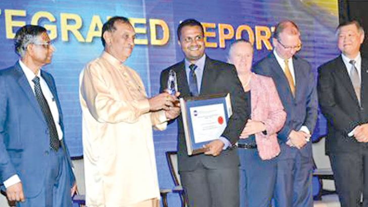 'Ten Best Integrated Reports' award being presented to PLC's Chief Manager, Finance, Omal Sumanasiri by the Speaker of the Parliament, Karu Jayasuriya