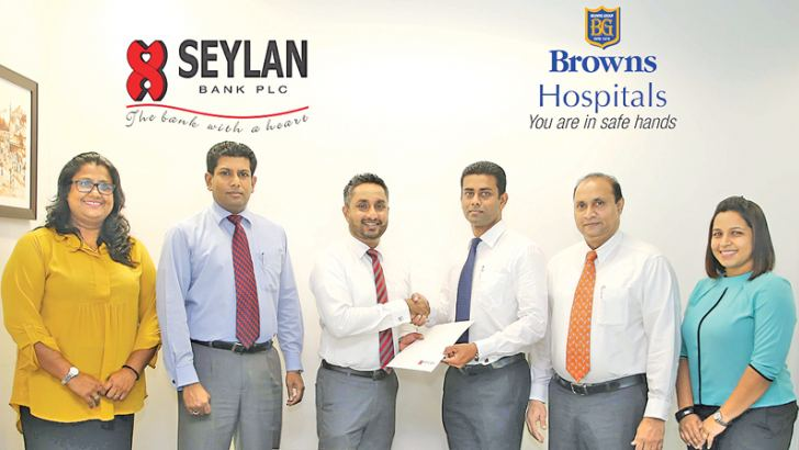 Seylan Bank Head of Marketing and Sales Gamika De Silva Exchanging the MoU with Browns Hospitals Chief Operation Officer Charitha Jayasinghe flanked by representatives of Seylan Bank and Browns Hospitals.