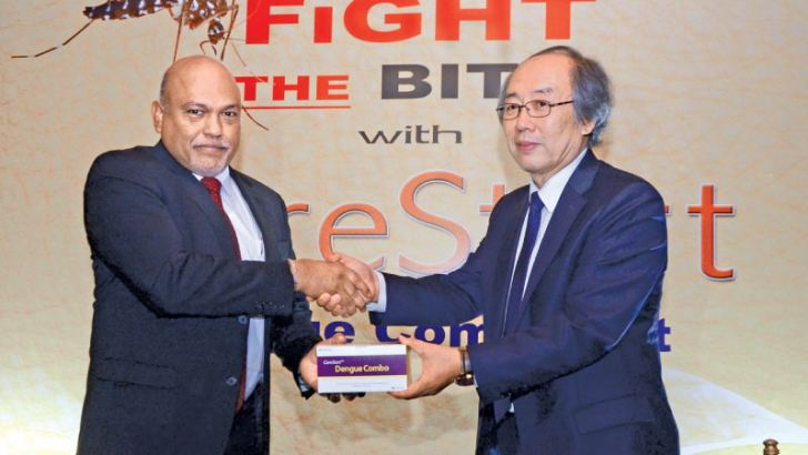 Dr. Byoung Don Han the Wells Bio CEO, presents a CareStart Dengue Combo Kit to the Chairman and Managing Director of Mega Pharma  Shirantha Peries.
