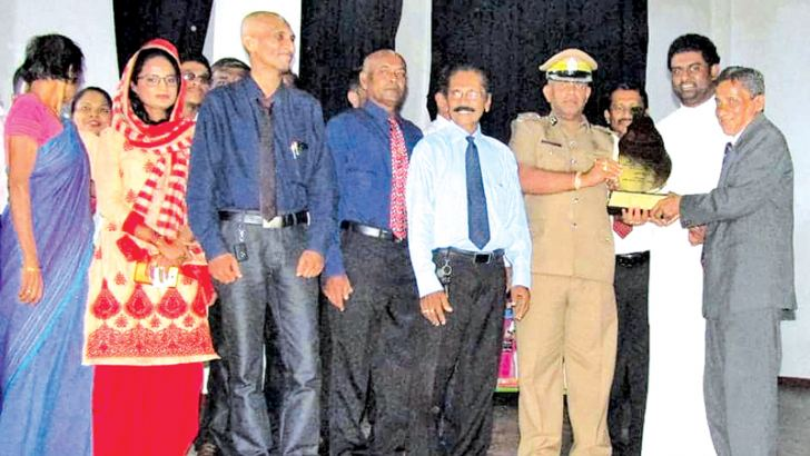 Justice and Prison Reforms Deputy Minister H..R.. Sarathie Dushmantha Mithrapala presents the award to Galle Prison Superintendent Chandana Weerasinghe. Picture by Mahinda P. Liyaanage