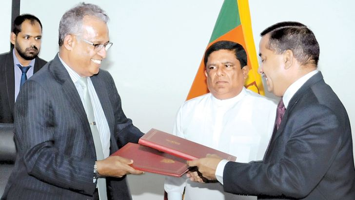 Foreign Affairs Ministry Secretary Prasad Kariyawasam and Home Affairs Ministry Secretary S.T. Kodikara exchange the MoU in the presence of Home Affairs Minister Vajira Abeywardena.