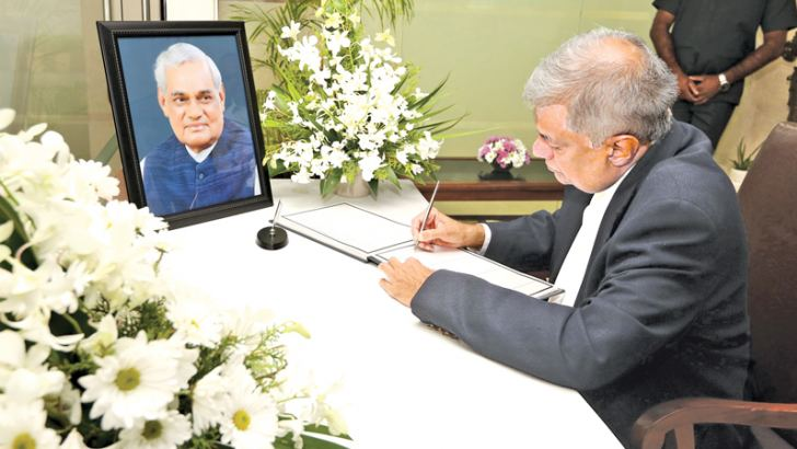 Prime Minister Ranil Wickremesinghe signs the condolence book.