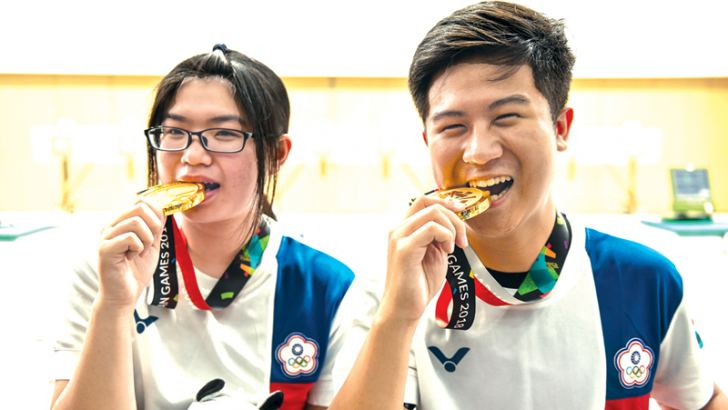 Gold medallists Taiwan's Lin Yingshin (L) and Lu Shaochuan pose with their medals after the victory ceremony for the 10m air rifle mixed team shooting final during the 2018 Asian Games in Palembang on August 19, 2018. AFP