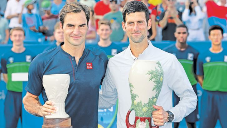Roger Federer of Switzerland and Novak Djokovic of Serbia pose for photographers after their match during the men's final of the Western & Southern Open at Lindner Family Tennis Center on Sunday. - AFP