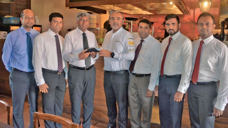 Assitant General Manager (Electronic Banking Centre),Emil De Silva, offering a UnionPay enabled EDC Terminal to Dharshan Munidasa Co-owner of MINISTRY OF CRAB Resaurant  as its first merchant for accepting UnionPay Cards looked on by members from Bank of Ceylon and MINISTRY OF CRAB Resaurant