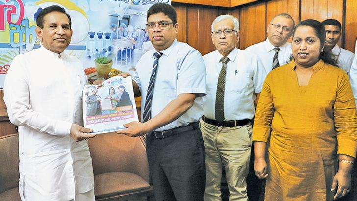 Lake House Chairman & Managing Director Krishantha Cooray presenting the first anniversary publication of the health journal 'Suwa Arana' to Health, Nutrition and Indigenous Medicine Minister Dr. Rajitha Senaratne. The first anniversary of 'Suwa Arana' issued free with Sinhala publication 'Dinamina,' was commemorated yesterday under the auspices of Minister Senaratne at Lake House premises. Lake House Editorial Director Attorney at Law Chandrasiri Seneviratne, General Manager Abhaya Amaradasa, Editor- Gover