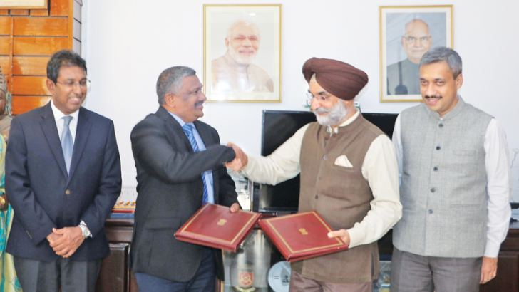 Indian High Commissioner to Sri Lanka Taranjit Singh Sandhu and National Policies and Economic Affairs Ministry Secretary K.D.S. Ruwanchandran exchanging the documents after signing the MoU in the presence of National Policies and Economic Affairs State Minister Dr. Harsha de Silva.