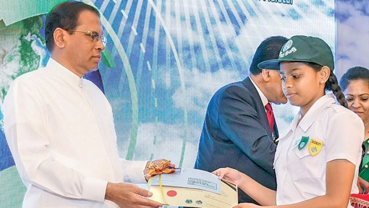 President Maithripala Sirisena presents a prize to a student at the International Ozone Day commemoration held at the BMICH, yesterday morning. Picture courtesy President's Media Division