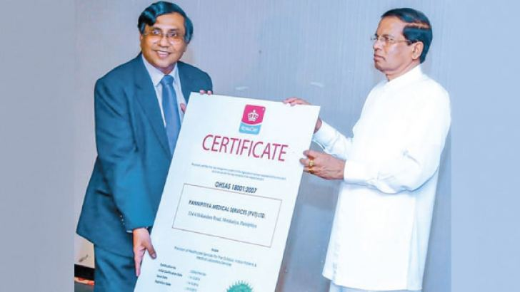 Pannipitiya Private Hospital Managing Director Ananda Kuruppuarachchi receives the Standard Certification from President Maithripala Sirisena.