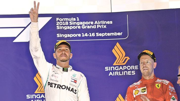 Singapore Formula One Grand Prix winner Mercedes' British driver Lewis Hamilton (L) opened up a 40-point lead in the F1 drivers' championship. Third placed Ferrari's German driver Sebastian Vettel is on right. AFP