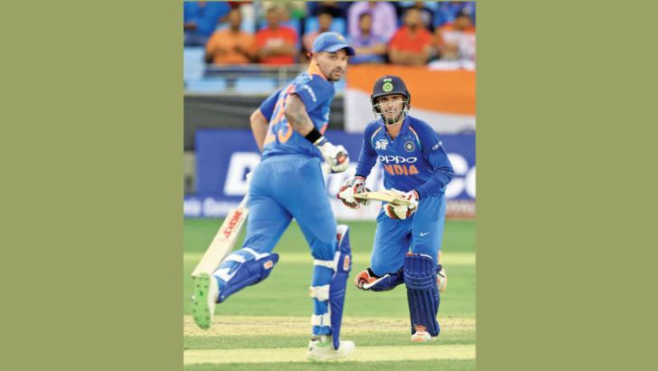 Indian batsmen Shikhar Dhawan (L) and Ambati Rayudu runs between the wickets during their century partnership in the Asia Cup cricket match against Hong Kong at the Dubai International Cricket Stadium on Tuesday. – AFP