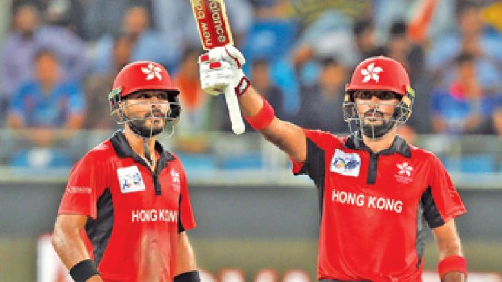 Hong Kong's batsman Nizakat Khan (R) celebrates after scoring a half-century as team captain Anshuman Rath looks on during the Asia Cup cricket match against India at the Dubai International Cricket Stadium on Tuesday. The pair added a record 174 runs for the first wicket. - AFP