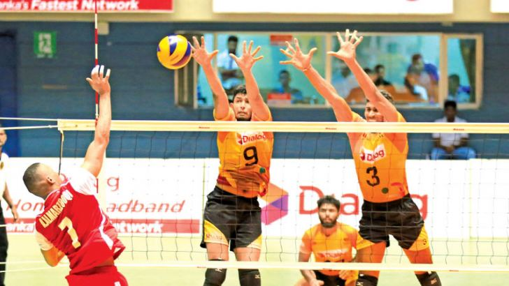 Sri Lanka's Ayesh Dilhan and Lasindu Methmal blocking the spiking from an Emirate spiker during  the quarter final match of the Asia Men's Volleyball Challenge Cup yesterday. Picture by Ranjith Asanka