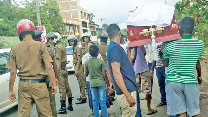 Youths carrying the victim's coffin along the Malabe - Godagama main road near Athurugiriya town.