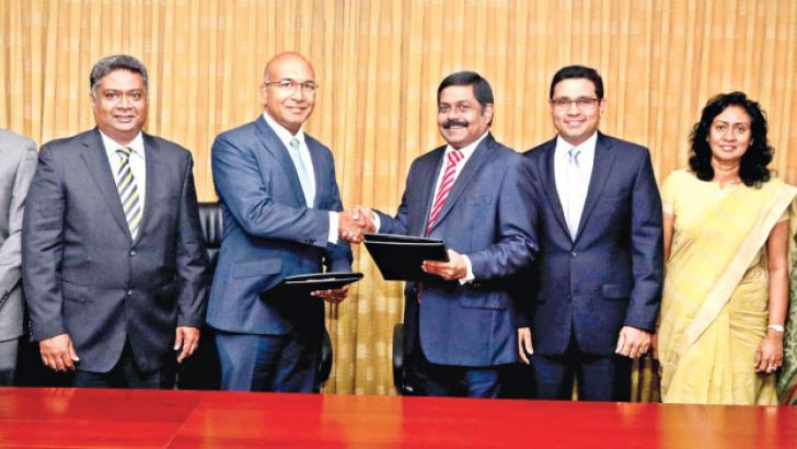 Commercial Bank Managing Director S. Renganathan and Asia Securities Holdings Chairman Dumith Fernando exchange the MoU in the presence of members of the management of the two companies.