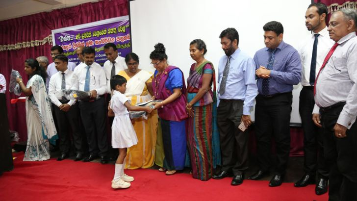 Sabaragamuwa Governor Niluka Ekanayaka handing over a scholarship to a student to carry out her 13-year continuous education. Ratnapura District Secretary Malani Lokupothagama, Governor's Secretary Rukmani Ariyaratne and others participated.