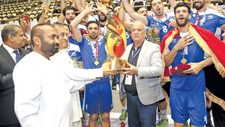 The Chief Guest on the final day of the Asia Men's Volleyball Championship Speaker of Parliament Karu Jayasuriya and minister of Power and renewable Energy and president of SLVF Ranjith Siyambalapitiya handing over the Champions Cup to coach of the Iraqi team Alaa Khalafa.