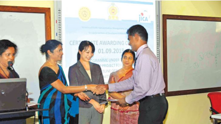 A senior government officer receives her certificate.